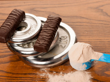 55159312 - whey protein powder in measuring scoop, protein bar, meter tape and dumbbell on wooden background.